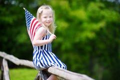 Hållande amerikanska flaggan för förtjusande liten flicka utomhus på härlig sommardag Arkivfoto