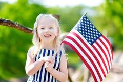 Hållande amerikanska flaggan för förtjusande liten flicka utomhus på härlig sommardag Arkivbild