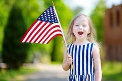 Hållande amerikanska flaggan för förtjusande liten flicka utomhus på härlig sommardag Arkivbilder