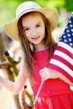 Hållande amerikanska flaggan för förtjusande liten flicka utomhus på härlig sommardag Royaltyfri Foto