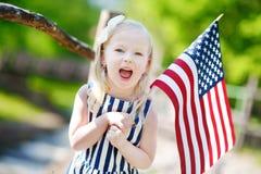 Hållande amerikanska flaggan för förtjusande liten flicka utomhus på härlig sommardag Royaltyfri Fotografi