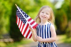 Hållande amerikanska flaggan för förtjusande liten flicka utomhus på härlig sommardag Royaltyfri Bild