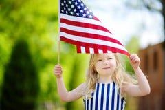 Hållande amerikanska flaggan för förtjusande liten flicka utomhus på härlig sommardag Fotografering för Bildbyråer