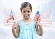Hållande amerikanska flaggan för flicka mot att fladdra amerikanska flaggan Royaltyfri Foto