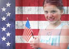 Hållande amerikanska flaggan för liten flicka mot amerikanska flaggan Royaltyfri Fotografi