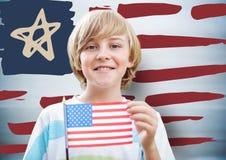 Hållande amerikanska flaggan för pojke mot den hand drog amerikanska flaggan och oskarp blå bakgrund Royaltyfria Bilder