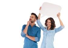 Hållande anförandebubbla för kvinna nära mannen som visar hans tankar Arkivbild