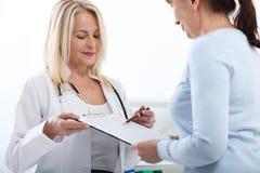 Hållande ansökningsblankett för kvinnlig doktor, medan konsultera patienten på sjukhuset arkivfoton