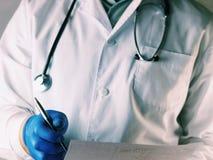 Hållande ansökningsblankett för manlig doktor, medan konsultera patienten Doktor i en vit maskering Doktorn rymmer en penna i han Royaltyfria Foton