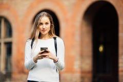 Hållande anteckningsböcker för ursnygg lycklig student som smsar på telefonen på universitetet Fotografering för Bildbyråer