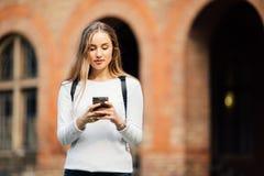 Hållande anteckningsböcker för ursnygg lycklig student som smsar på telefonen på universitetsområdet på högskolan Arkivbild