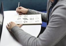 Hållande anteckningsbok för hand med Drew Brand Logo Creative Design idéer fotografering för bildbyråer