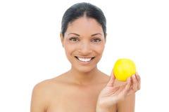 Hållande apelsin för gladlynt svart haired modell Arkivfoto