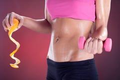 Hållande apelsin för konditionkvinna och vikter, sunt livbegrepp Arkivbild