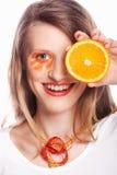 Hållande apelsin för kvinna på hennes öga Royaltyfri Bild