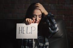 Hållande ark för deprimerad kvinna av papper med ordet HJÄLP Fotografering för Bildbyråer
