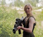 Hållande armévapen för härlig sexig blond kvinna Royaltyfria Bilder