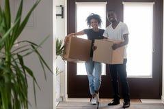 Hållande askar för svarta par som står i hallet som ser kameran royaltyfri bild