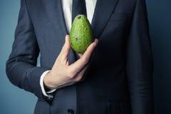 Hållande avokado för affärsman royaltyfria foton