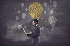 Hållande bärbar dator för affärsman som är främst av svart tavla med ballongen royaltyfri fotografi