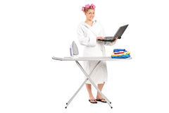 Hållande bärbar dator för flicka bak strykbräda Royaltyfri Foto