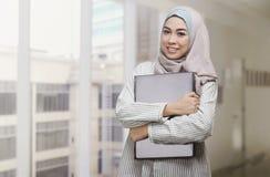 Hållande bärbar dator för härlig asiatisk muslimkvinna Royaltyfri Fotografi