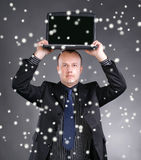 Hållande bärbar dator för ung affärsman på hans huvud Royaltyfria Foton