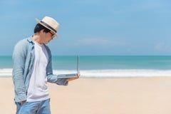 Hållande bärbar dator för ung asiatisk man på stranden royaltyfri bild