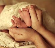 Hållande babys för moder fot i händer Royaltyfri Bild