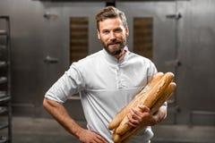 Hållande bagetter för bagare på tillverkningen arkivbilder