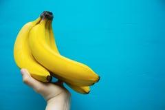 Hållande bananer för hand Arkivbilder