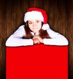 Hållande baner för julflicka över träbakgrund royaltyfria foton