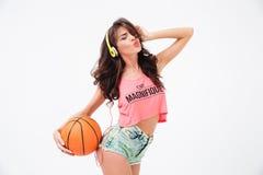 Hållande basketboll för sexig kvinna och lyssnande musik i hörlurar royaltyfri fotografi