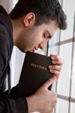 Man som ber vid fönstret Arkivfoto