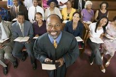 Hållande bibel för predikant med kongregationsammanträde i kyrka royaltyfri bild