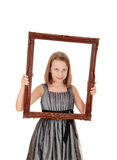 Hållande bildram för nätt flicka royaltyfri foto