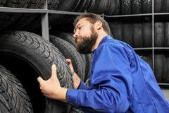 Hållande bilgummihjul för manlig mekaniker Arkivbild