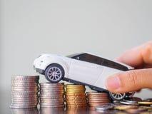 Hållande bilmodell för hand på bunt av mynt Royaltyfri Fotografi
