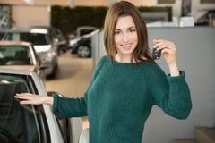 Hållande biltangent för kvinna inom bilåterförsäljaren arkivfoton