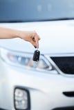 Hållande biltangent för kvinnlig hand med pov på bakgrund Royaltyfria Bilder