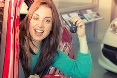 Hållande biltangent för ung kvinna inom bilen Royaltyfri Foto