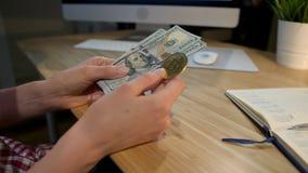 Hållande bitcoin för kvinna och bunt av kassa Skördsikt av kvinnliga händer som rymmer metallbitcoin och packen av dollarsedlar arkivfilmer