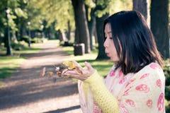Hållande blad för kvinna i en parkera Arkivbilder
