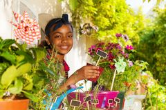 Hållande blomkruka för afrikansk flicka med växtetiketten royaltyfria foton