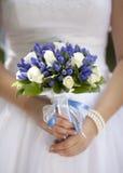 Hållande bröllopbukett för brud Arkivbild