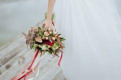 Hållande bröllopbukett för brud på bröllopceremoni Arkivfoto