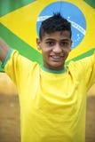 Hållande brasiliansk flagga för stolt patriotisk ung brasiliansk fotbollsfan arkivbilder