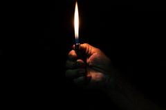 Hållande brinnande tändare för gamal manhand Royaltyfri Bild