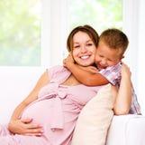 Hållande buk för barn av gravid kvinna Royaltyfri Foto