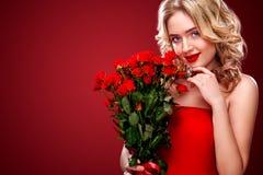 Hållande bukett för härlig blond kvinna av röda rosor Internationell dag för kvinna` s åtta beröm för mars Arkivfoto